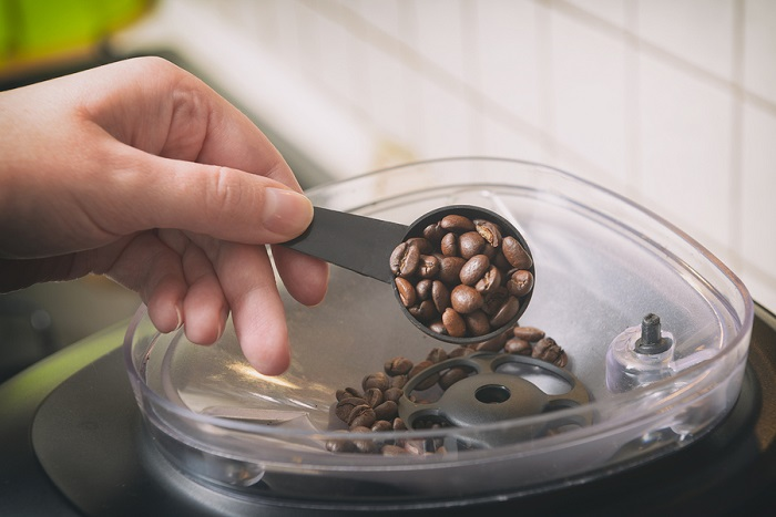 Adding-coffee-beans-to-the-built-in-grinder-in-the-automatic-espresso-machine