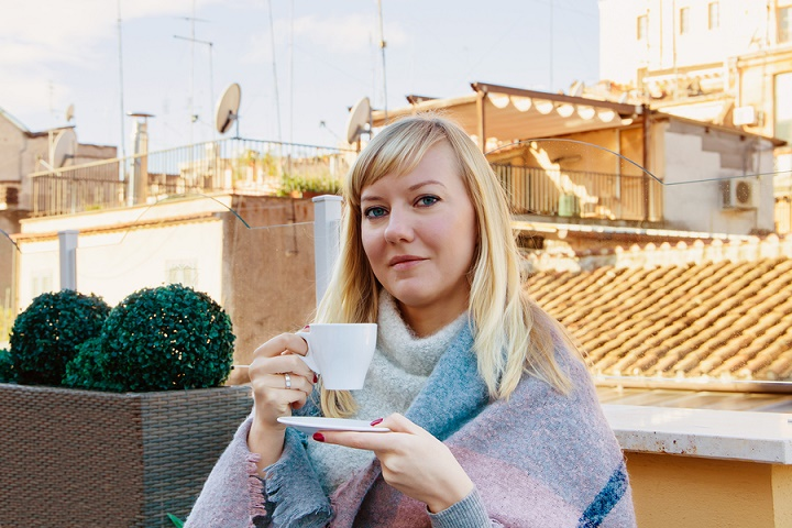 Romantic-woman-enjoying-a-cup-of-coffee-on-a-roof-terrace-in-Rome
